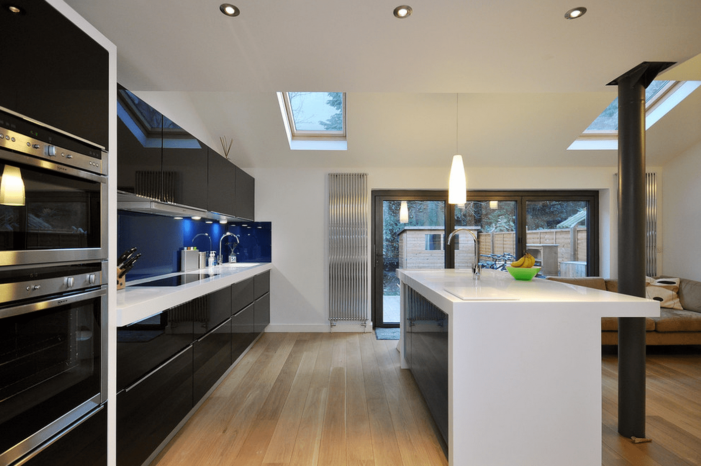 Black Furniture: Interior Design Photo Ideas. Light wall finishing of the kitchen with the wall-long solid black furniture set with glossy surfaces