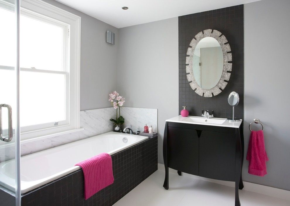 Black Furniture: Interior Design Photo Ideas. Bathroom in the contemporary minimalistic style and dark backsplash of the bathtub, black cabinet and the trimming of the accent wall