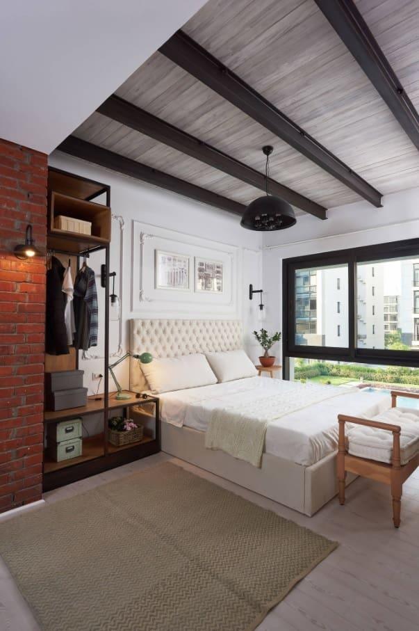 Exposed custom closet wardrobe in loft bedroom with black ceiling beams