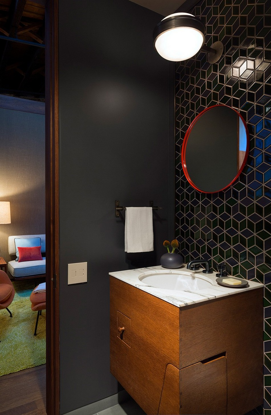 Dark decorated bathroom with the red frame of the mirror
