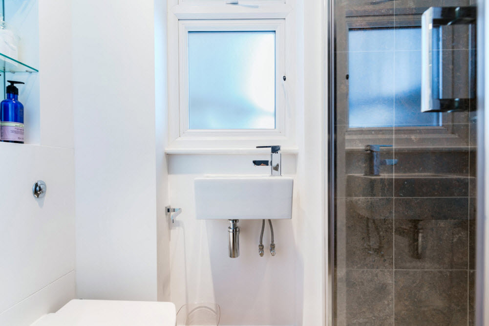White trim and sink in the bathroom of very small apartment