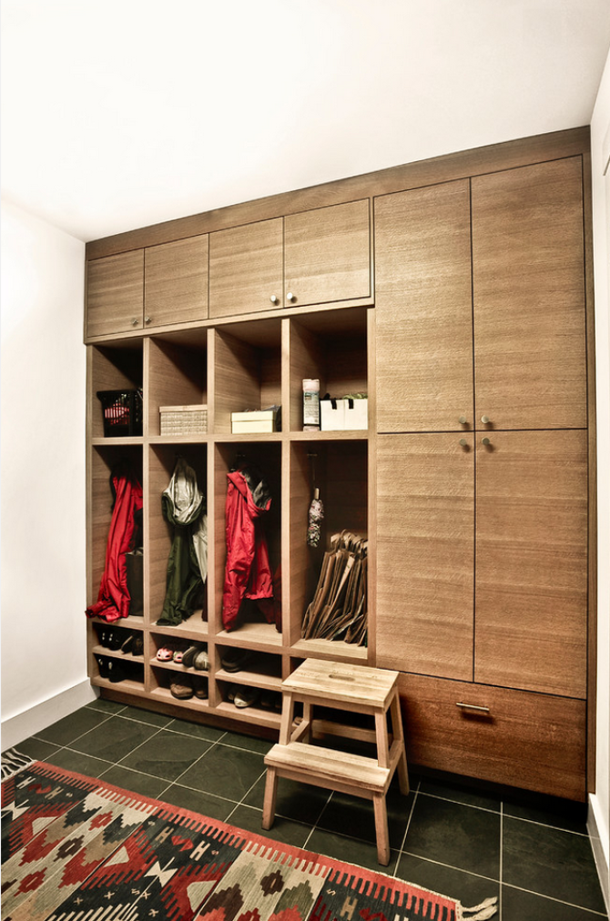 A whole wooden cabinet for the clothes in the white minimalistic entry