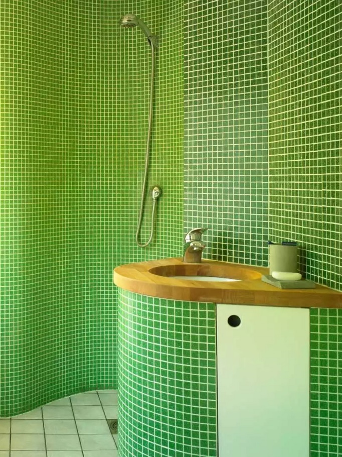 Green mosaic tile bathroom looks like reception in the hotel