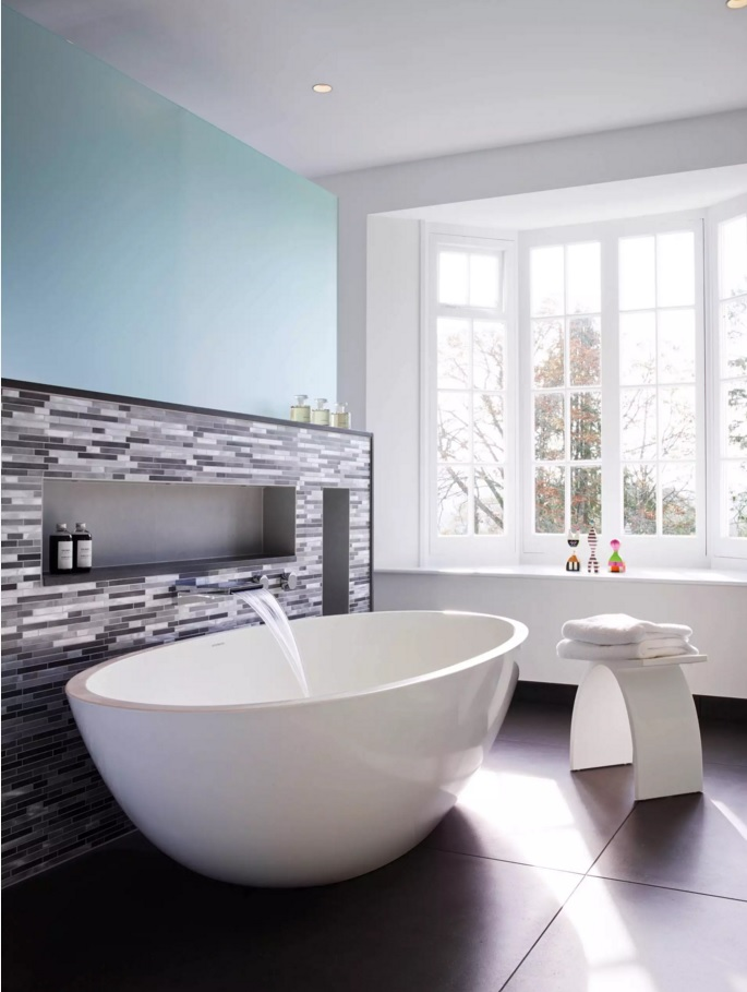 Round bathtub and same formed round stool in the nicely decorated light bathroom