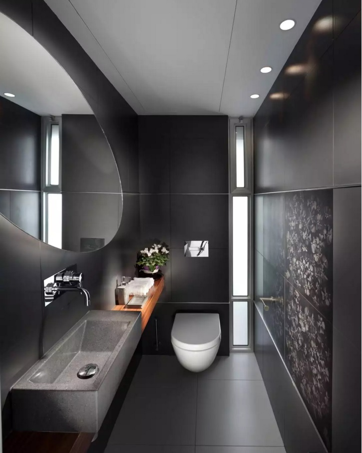 Dark styled bathroom with huge round mirror and hovering toilette