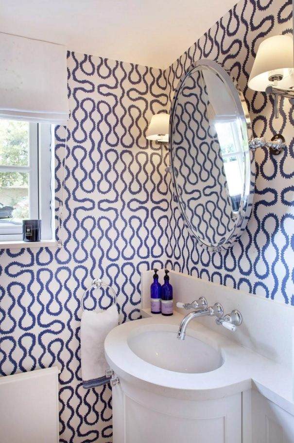 Unique blue impressionsitic pattern of the wallpaper in tight bathroom with hanging mirror