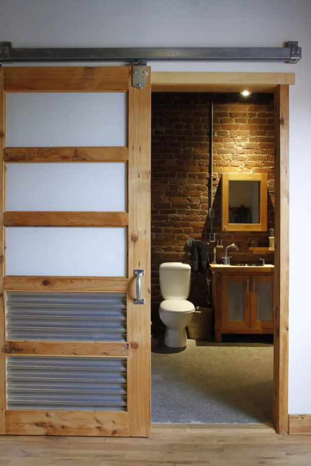 Nice loft design of the bathroom in loft style with the sliding door