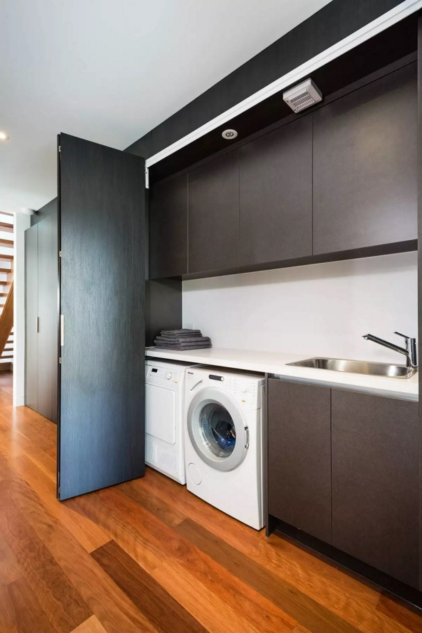 Functional and Beatiful Laundry Interior Ideas. Nice dark door to hide the appliances or to zone the space