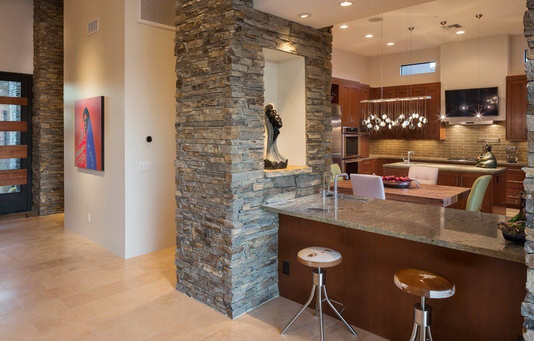 Accent stone trimmed separating wall in the wooden trimmed modern kitchen interior