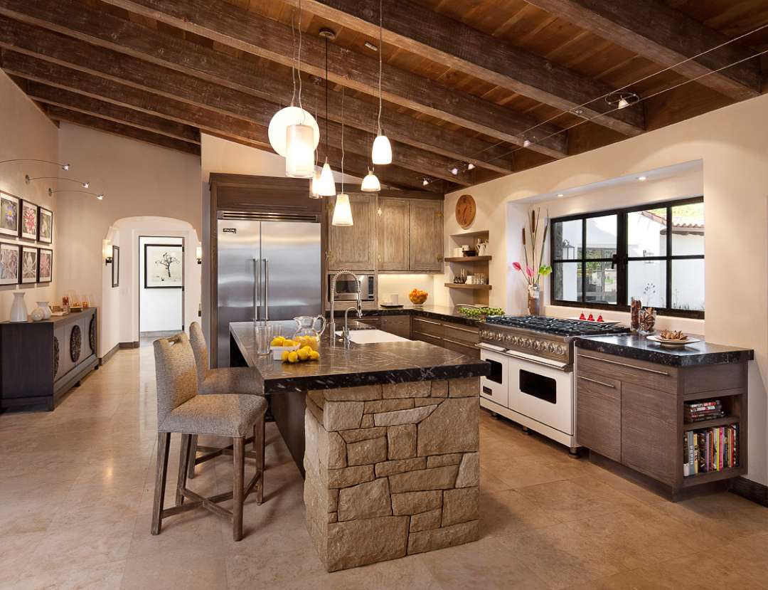 Sloped wooden ceiling with opened beams of the country style looks charming with stone trimmed island in the middle