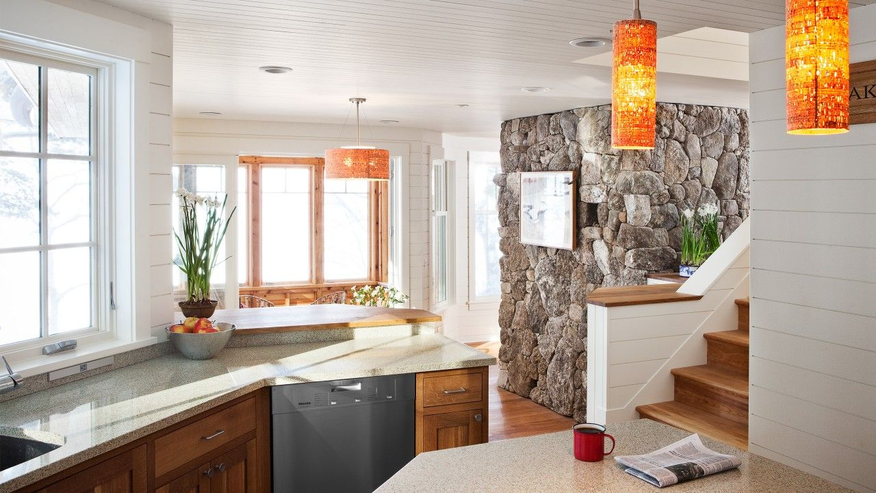 White and full of light kitchen interior with the stone faced accent wall