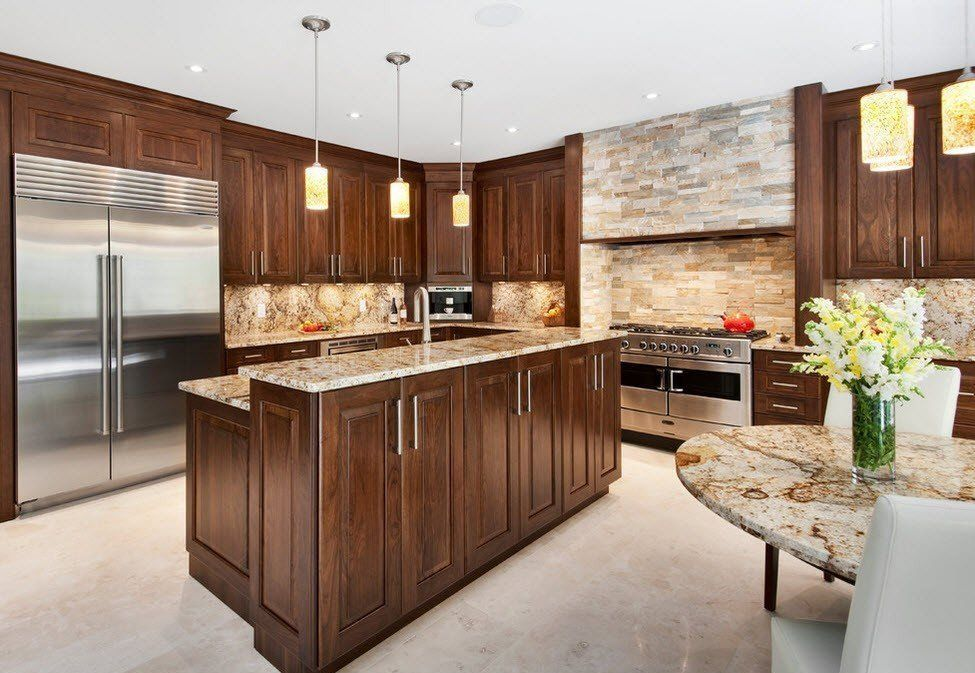 Stone Kitchen Interior Decoration Ideas. Nice wooden surfaces of the furniture of the island blends well with crude stone