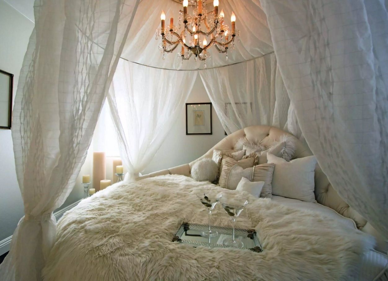 Circle Bed of Unique Bedroom Interior Design. Royal sleeping area with candle chandelier above it