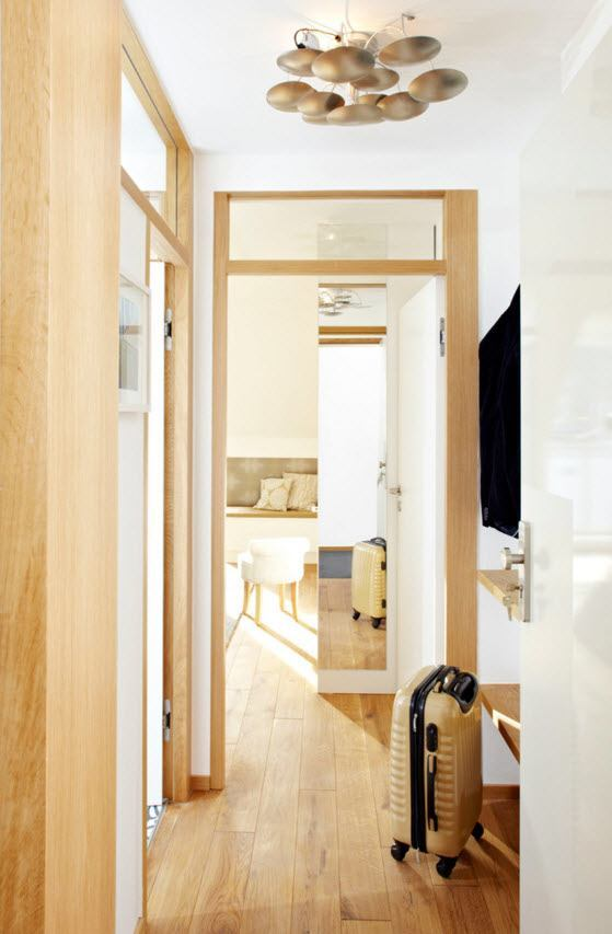 Small Apartment Light Color Design Theme. Natural wooden door frame and the creamy trimming if the interior
