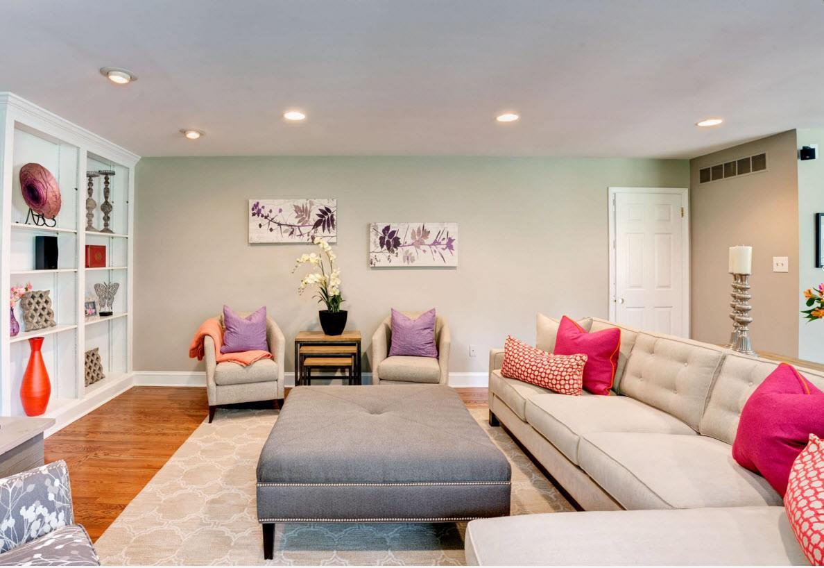 Nice fresh bright living interior with original gray ottoman in the center still looks spacious