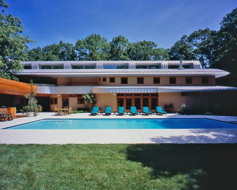 Original Architecture of Private House with In-ground Pool. Azure water and blue sunbeds at the sultry summer day