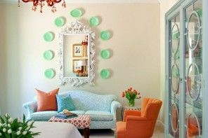 Turquoise decorative plates in the Shabby chic interior with orange armchairs