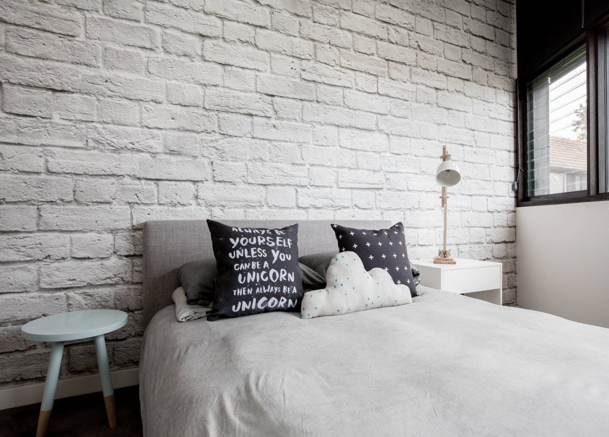 Neatly whitewashed vrick wall in the calming modern design of the bedroom