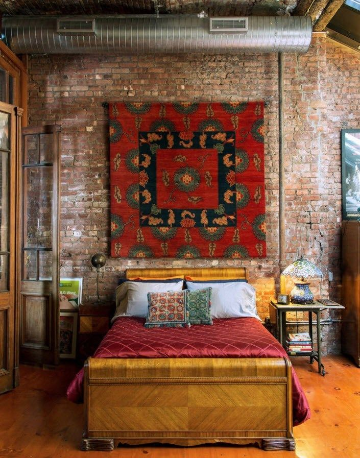 Original tapestry blends well with the brickwork of the accent wall in the bedroom