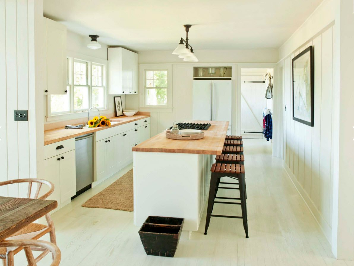 Wooden countertops in the kitchen are perfectly blend with white environment