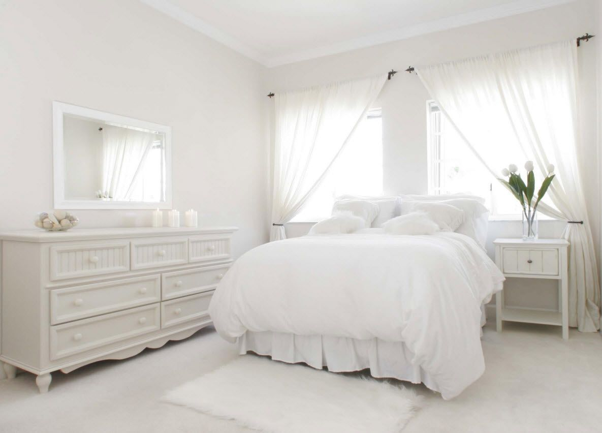 Absolutely white sterile bedroom space with intimate tulle in the windows