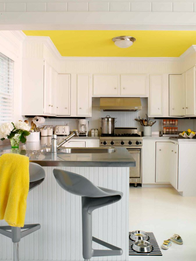 White Floor as an Exquisite Decoration Idea for Modern Interiors. Modern kitchen with untypical look and yellow accents of ceiling and furniture