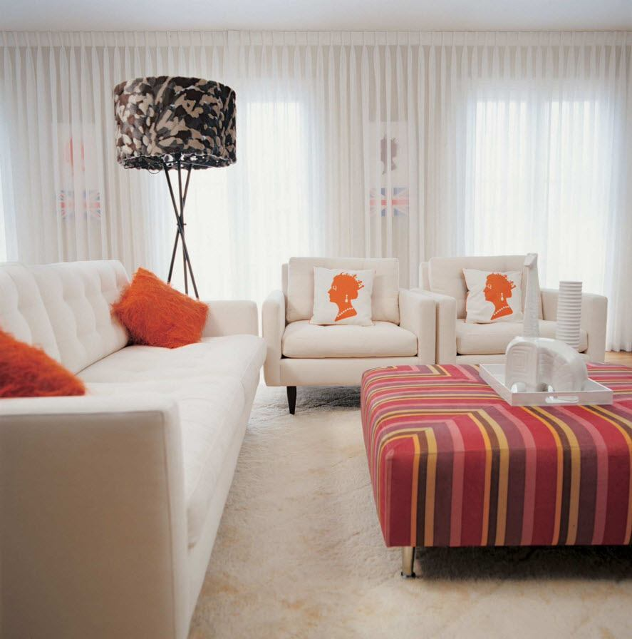 Red striped ottoman in the light living room with bright accents on the cushions