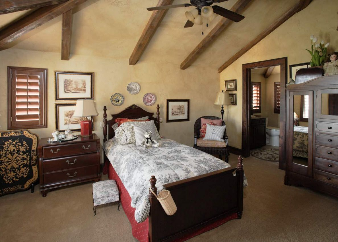 Rustic style in the private house bedroom with opened ceiling beams, creamy walls and decorative plates at the headboard