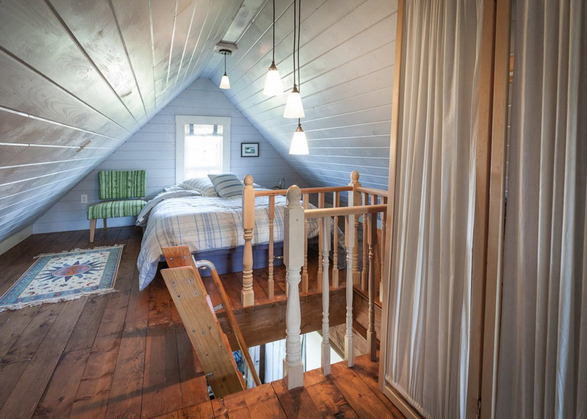Loft Style Bedroom Design at the Attic. Unusual form of stairs with wooden handrails