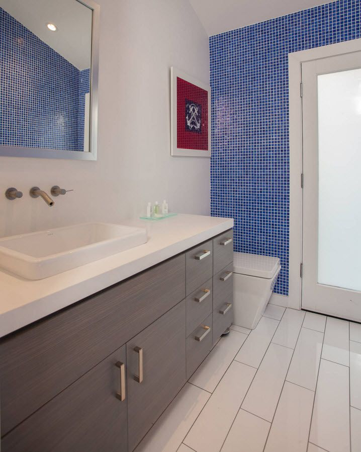 Beige textured wooden surfaces of the bathroom vanity with the red picture and blue accents on the walls