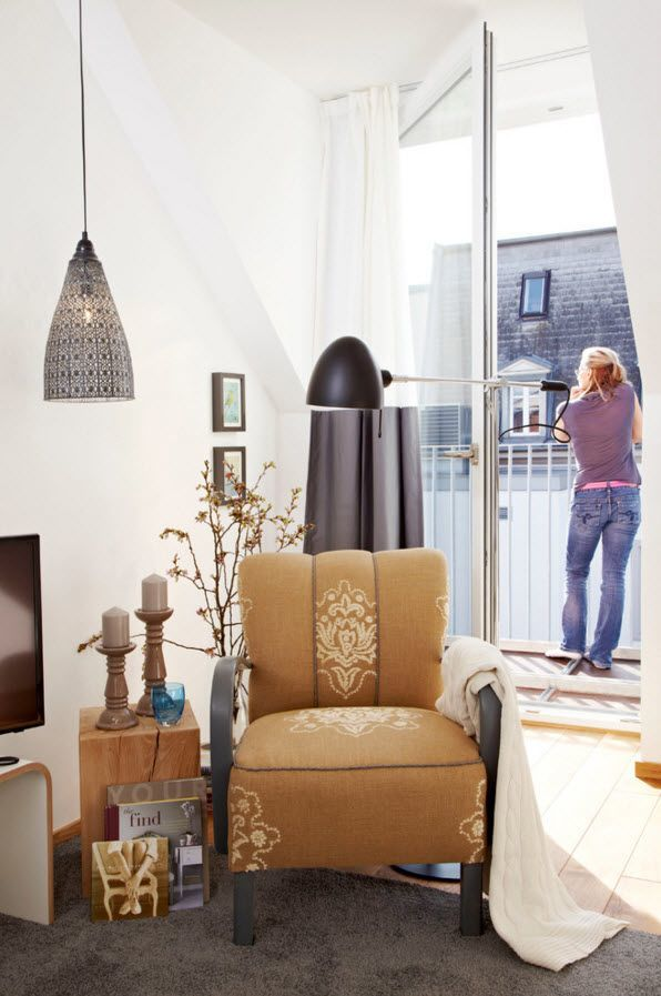 Small Apartment Light Color Design Theme. Soft armchair and perspective to the balcony