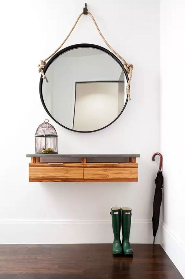 Cozy minimalsitic design of the mirror and bright lacquered wooden drawer against the white wall