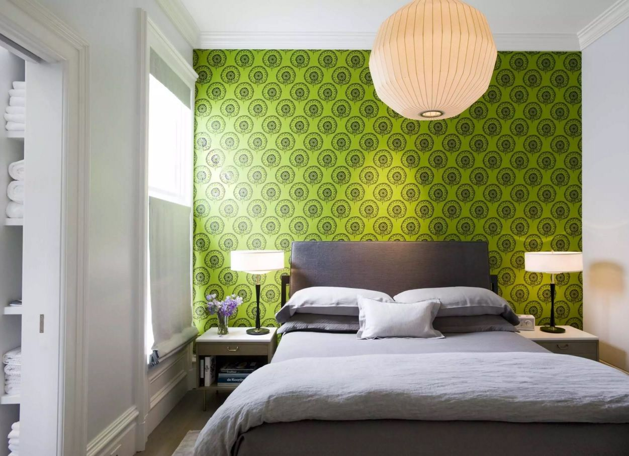 Small bedroom with accent green wall and round lamp shade looks gorgeous