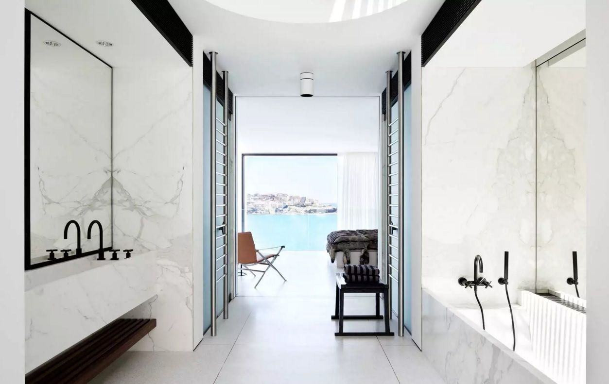 Black and white design of the open-layout bathroom with the entrance to loggia