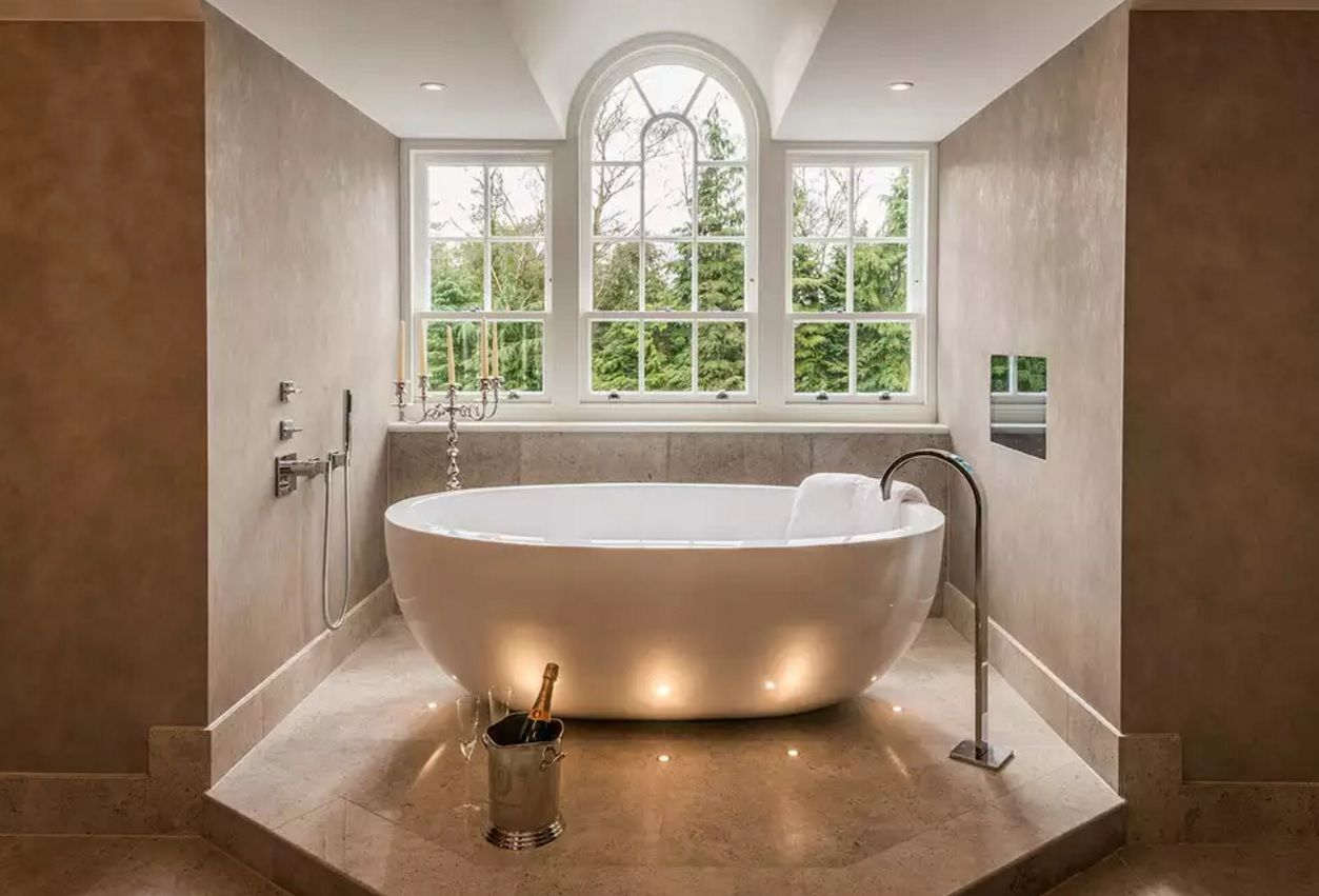 Bathroom Tap and Sink Ideas as an Interior Decoration Elements. Romantic classic variant of the bathtub surrounded by candles and the unusually designed crane