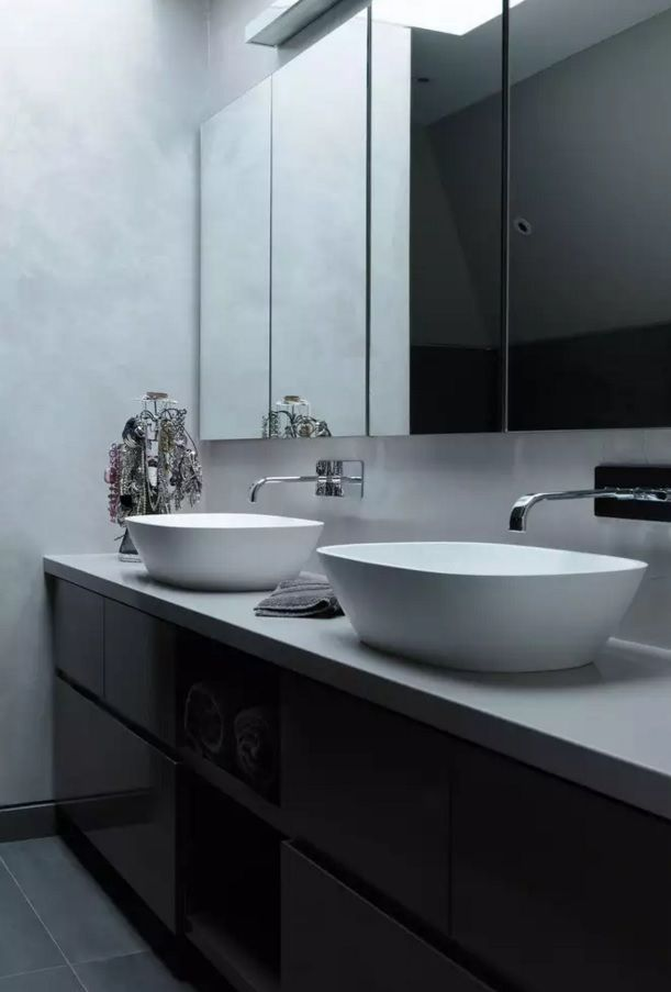 Original form of tap and sink in the contemporary styled bathroom with plenty of mirror surfaces