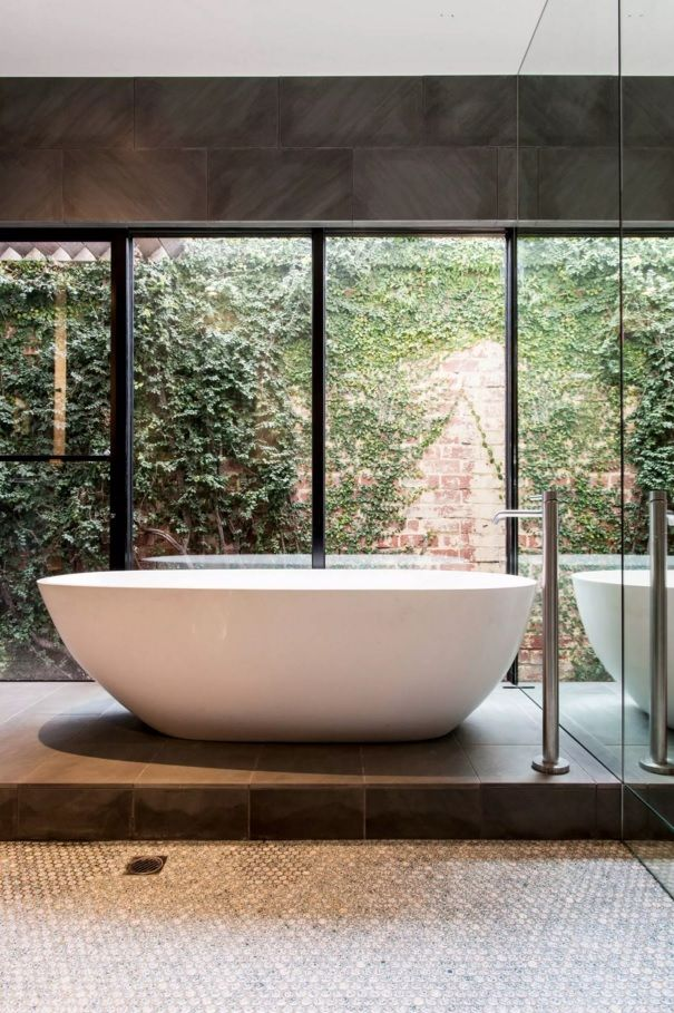 Panoramic windows and plenty of natural light with the central bathtub in spacious bathroom and hi-tech chromed tap
