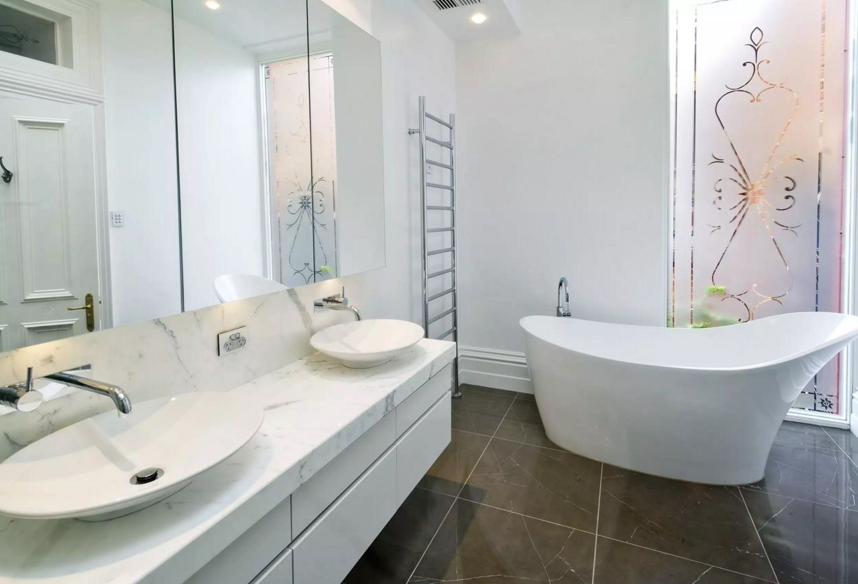 Ideally white bathroom with the all functional segments and dark contrasting large glossy floor tiles