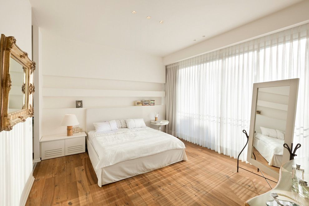Absolutely calm and pleasing atmosphere in the bedroom with panoramic windows behind the tulle curtains