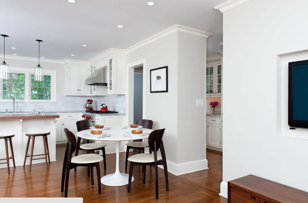 White kitchen trim and black contrasting backrests of the wooden chairs