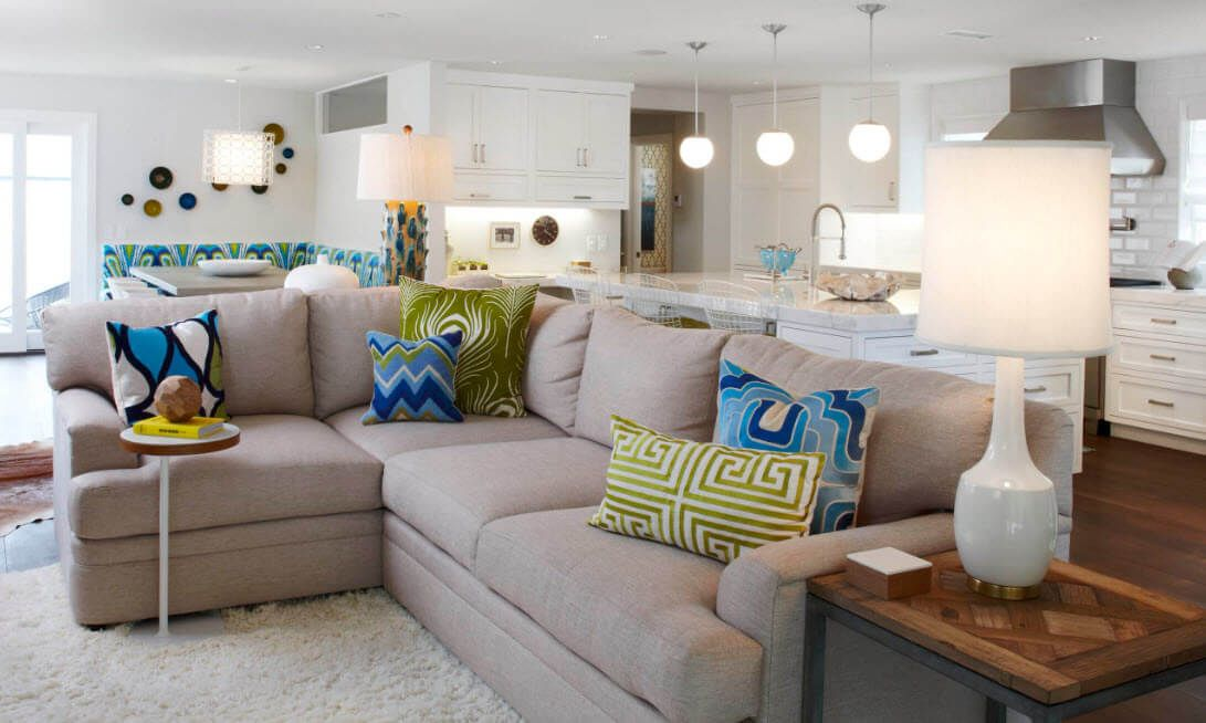 Studio apartment with the large angular sofa at the living zone with a lot of cushions