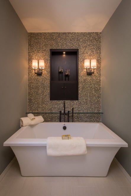 Gray mosaic accetn wall with lighting fixtures and white acrylic tub