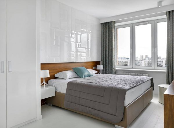 Textured white glossy walls and effective gray coverlet and light mattress