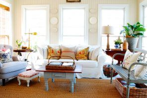 Nice living room decorated with a lot of wall plates and pillows and with the nice wooden coffee table