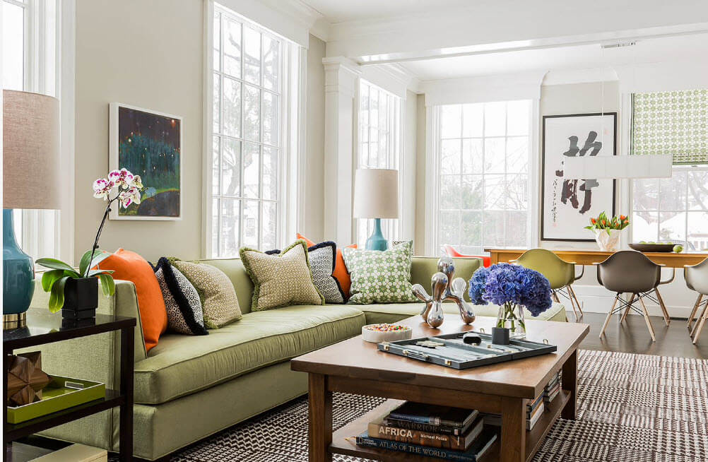 Olive color of the sofa along with the colorful pillows