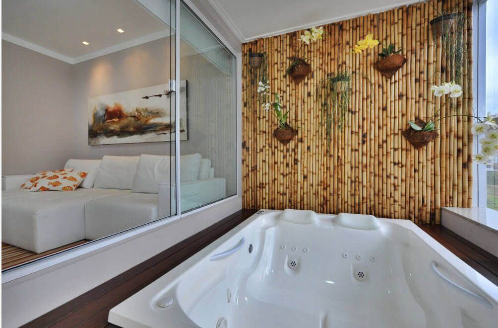 Snow white jacuzzi with headrests and hydromassage separated from bedroom with glass partition