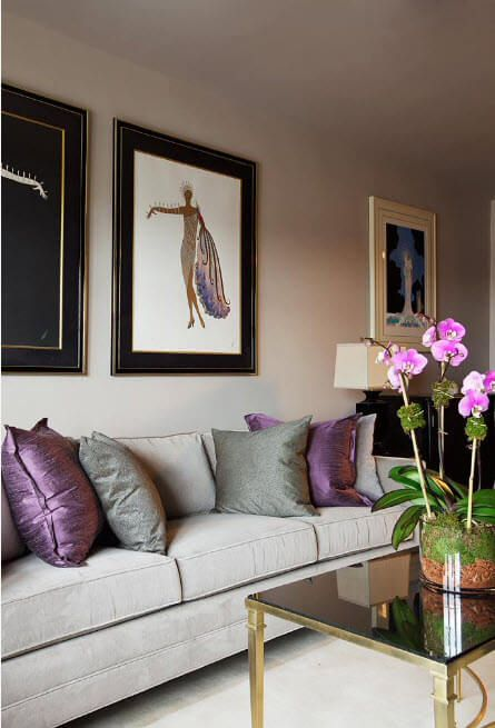 low-key design with photo reproductions on the wall and purple and gray pillows on the sofa
