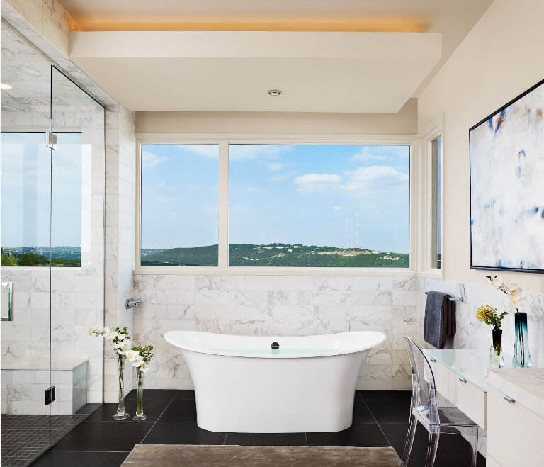 Deep acrylic tub at the panoramic window of modern light finished bathroom