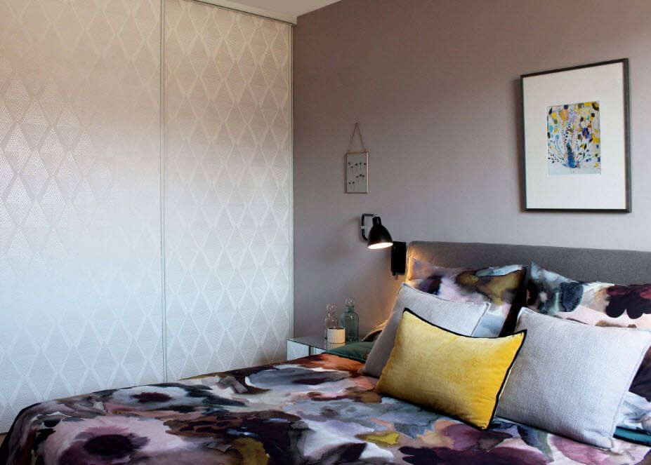 Cozy and artistic interior of the sleeping room with bright coverlet