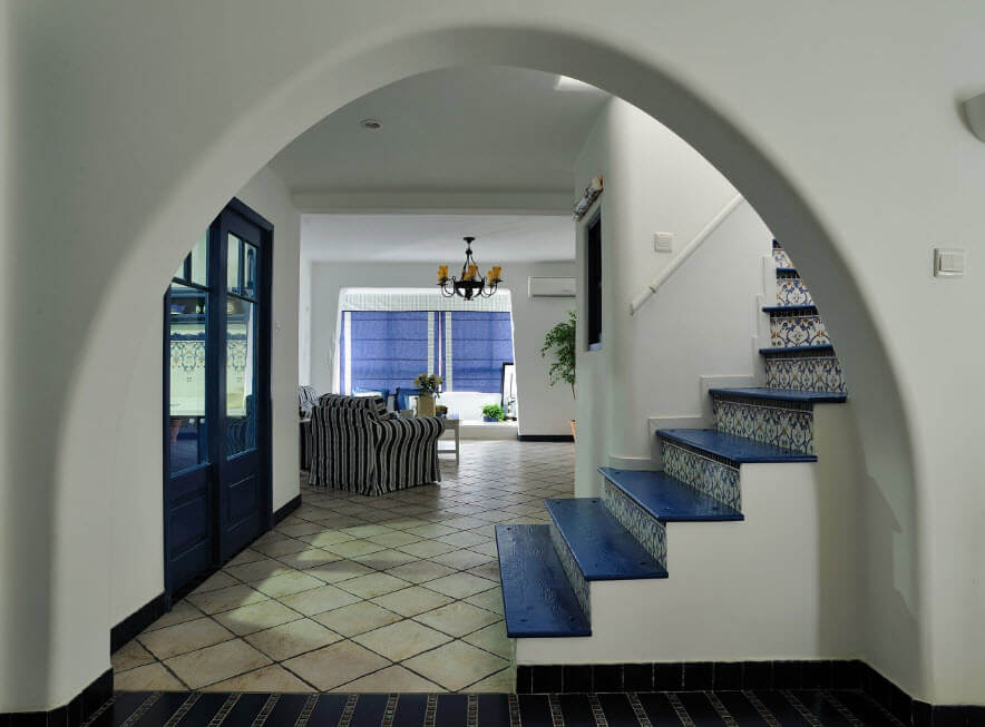 Nice house interior with arch and blue steps of the stairs